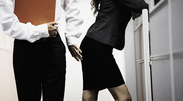 Businessman Touching a Businesswoman Inappropriately