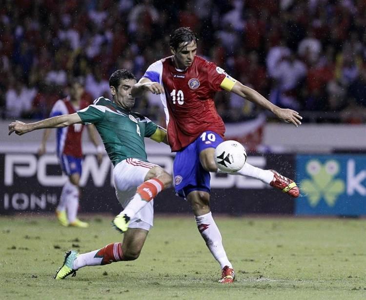 El jugador mexicano Rafael Márquez (i) marca al costarricense Bryan Oviedo (d) hoy, martes 15 de octubre de 2013, durante un partido clasificatorio al mundial de fútbol Brasil 2014, en San José (Costa Rica). EFE/Jeffrey Arguedas
