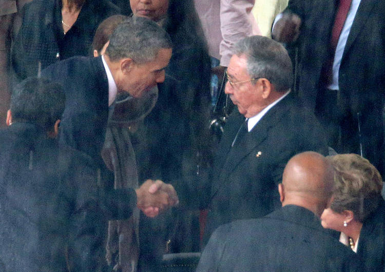 U.S. President Barack Obama (L) shakes hands with Cuban President Raul Castro during the official memorial service for former South African President Nelson Mandela at FNB Stadium December 10, 2103.