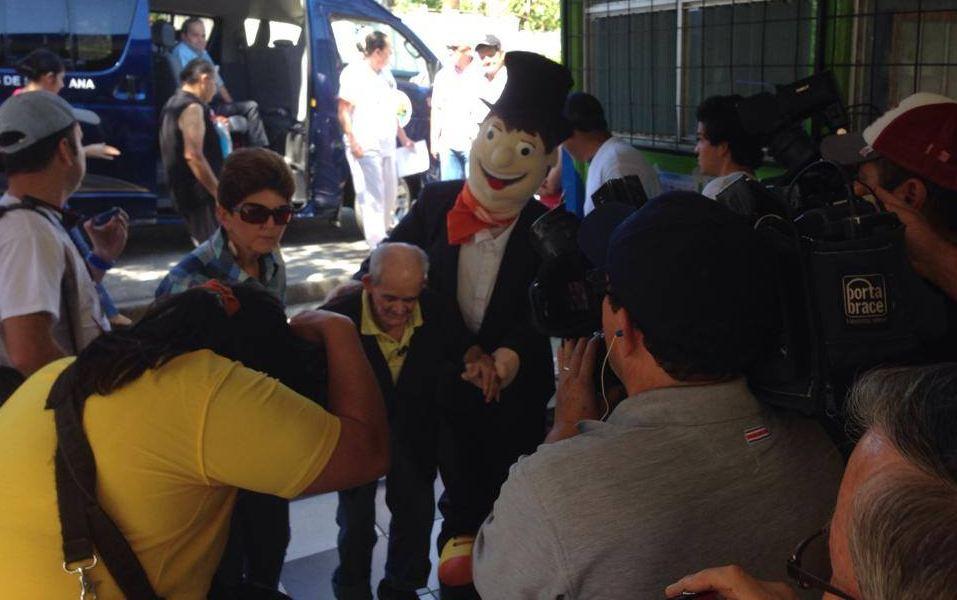 Armando Broncas ayudando a trasladar a Chepito, el tico más viejito con 113 años, quien pronto votará en Piedades de Santa Ana.