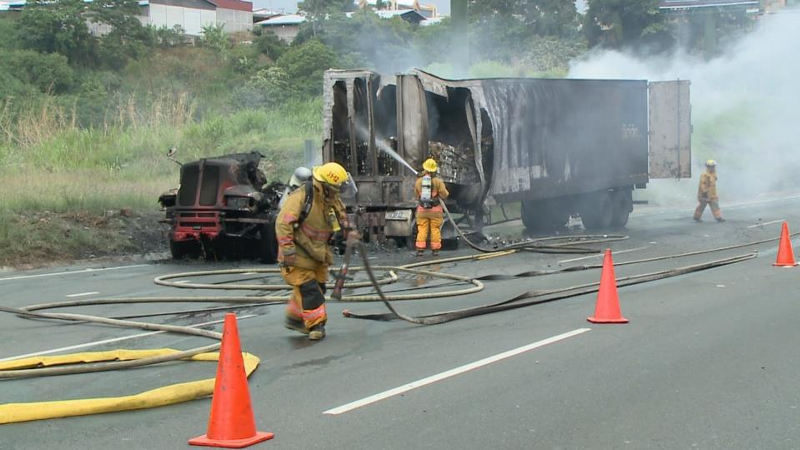 Bomberos (fire fighters) attend to a truck that burst in flames on the Ruta 27 Friday afternoon.