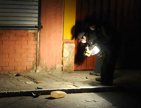 A Guatemalan police officer searches for evidence at a crime scene where a victim was lynched in Guatemala City. (Johan Ordóñez/AFP)