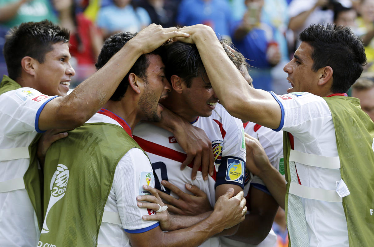 Costa Rica's Bryan Ruiz, centre, is congratulated by team mates after scoring his side's first goal over Italy's goalkeeper Gianluigi Buffon during the group D World Cup soccer match between Italy and Costa Rica at the Arena Pernambuco in Recife, Brazil, Friday, June 20, 2014. (AP Photo/Ricardo Mazalan)