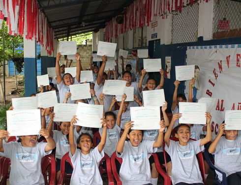 "Students at Cantón el Ojushte School in El Salvador's Usulután department display their certificates of participation in the ""Educating Resistance and Gang Membership by Children and Youths"" program. (Gloria Cañas for Infosurhoy.com)"