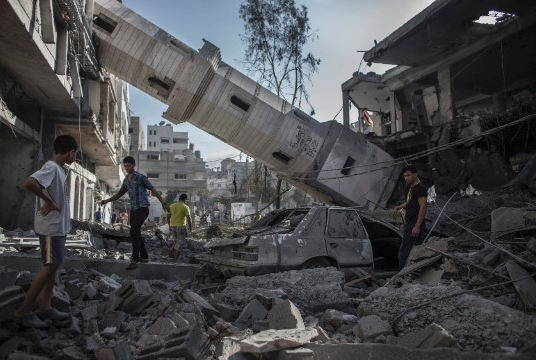 Palestinians walk under the collapsed minaret of a destroyed mosque in Gaza City on Wednesday, July 30. | Photo: CNN