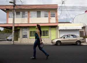 """In this July 9, 2014 photo, a woman walks in front of the building that once housed the human rights group Fundacion Operacion Gaya Internacional in Heredia, Costa Rica. Fernando Murillo was the charismatic head of the group and he'd been contracted by Creative Associates to turn Cuba's politically apathetic young people into """"change agents."""" Murillo was an idealist devoted to human rights. A former boy scout, he had no experience in undercover work, yet would soon face off against one of the world's most sophisticated"""