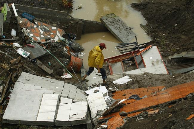 On Oct. 17, 2011, a man walks over his house, which was destroyed by a hurricane in Desamparados, south of San Jose, Costa Rica.