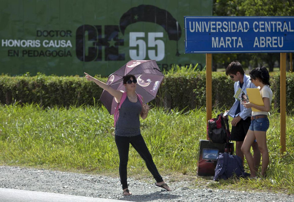 """In this July 11, 2014, photo, a Cuban student tries to flag down a taxi at the exit of Marta Abreu Central University in Santa Clara, Cuba. Beginning as early as October 2009, a project overseen by the U.S. Agency for International Development sent Venezuelan, Costa Rican and Peruvian nationals to Cuba to cultivate a new generation of political activists. Often posing as tourists, the young travelers befriended Cuban students. Fernando Murillo, contracted to turn politically apathetic young Cubans into """"change agents,"""" headed to Santa Clara and connected with a cultural group that called itself """"Revolution."""" (AP Photo/Franklin Reyes)"""