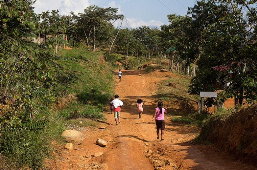 A Costa Rican indigenous family runs to take shelter in the community of Cedror in the indigenous territory of Salitre on Jul. 6, afraid of being attacked by landowners who occupied their land after setting fire to their homes and belongings the day before. Credit: David Bolaños/IPS