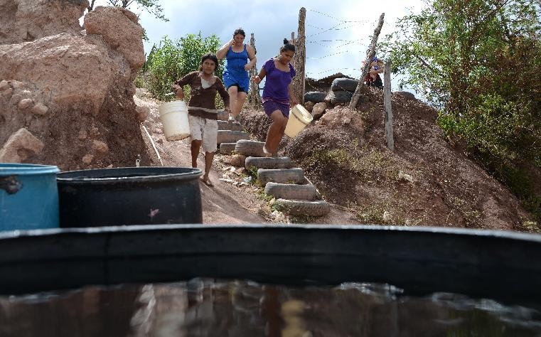 Women walk to collect water after a tanker filled containers in a poor neighbourhood on the outskirts of Tegucigalpa on August 7, 2014 Read more at: http://phys.org/news/2014-08-drought-central-america-crops-cattle.html#jCp