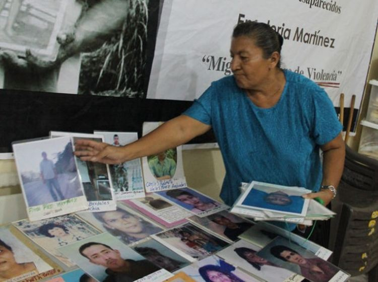 Rosa Nelly Santos arranges photos of missing Honduran migrants on a sort of shrine to ensure they are not forgotten, at the premises of the Committee for Disappeared Migrant Relatives in El Progreso. Credit: Thelma Mejía/IPS