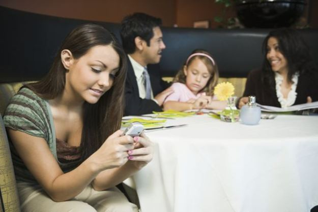 Family in restaurant, teenage girl (14-16) reading text message