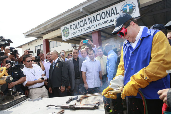 Destroying illegal firearms: Panamanian President Juan Carlos Varela Rodríguez helps destroy one of 100 firearms which gang members and other people surrendered to police in San Miguelito. Panamanian authorities announced a truce with gangs in July, and asked gang members to turn in their weapons. Authorities received hundreds of weapons. [Photo: Presidency of the Republic of Panama]