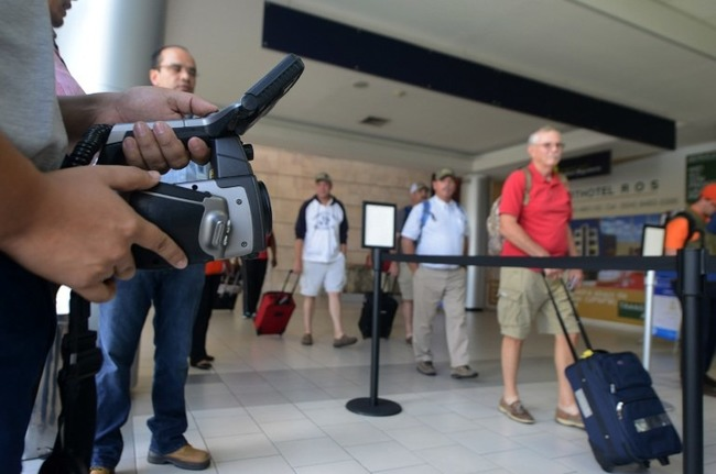 Fighting Ebola: Professionals from the International Health Surveillance Office (OSVI) at Toncontín International Airport in Tegucigalpa monitor arriving passengers for possible Ebola infection. It is one of the measures Honduras is taking to prevent an outbreak of the deadly virus. [Photo: AFP/Orlando Sierra]