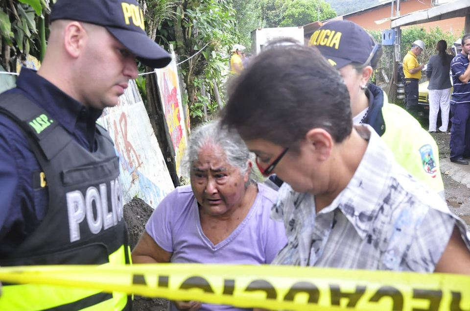 Police and neighbours console the grandmother in whose care the children were in. Photo: Franciso Barranted, La Nacion