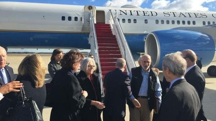 Gross, facing the camera in a blue shirt, flew back from Cuba on a US government plane