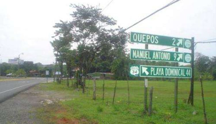 A sign at the intersection that leads to the town of Quepos and Dominical