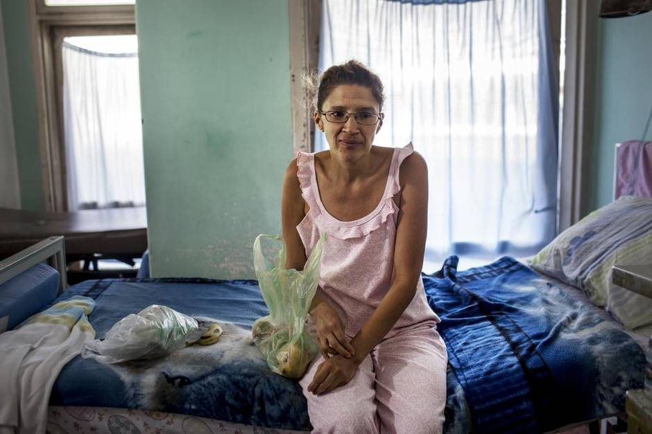 A patient holds a bag containing food and water that her sister brought her while she waits for care in a hospital in Caracas. Doctors have reported debilitating shortages of supplies – sheets, food, surgical gloves, antibiotics – needed to care for patients. (Natalie Keyssar for The Globe and Mail)
