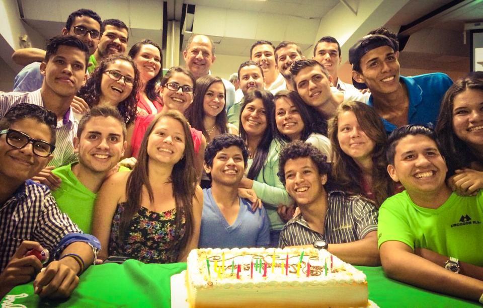 President Luis Guillermo Solis (in the way back, balding) was surprised with a birthday cake by young cooperatives in Alajuela. Photo: Facebook