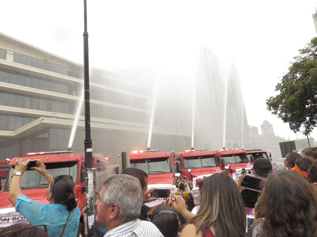 After the blessing of the fire trucks, the firemen let loose with their sirens and shot a spray of water into the air.