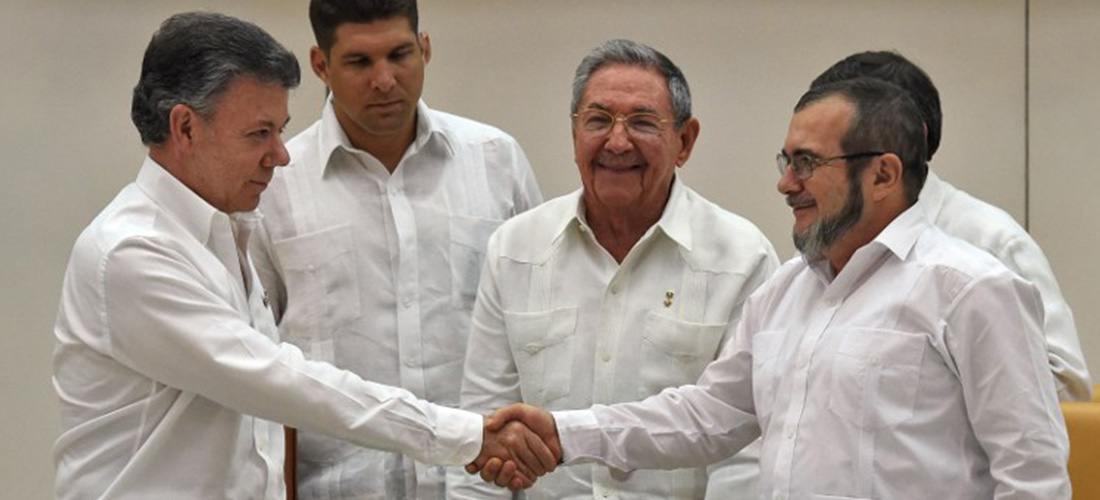 "Colombian President Juan Manuel Santos (left), shakes the hand of FARC leader Timoleom Jimenez, alias ""Timochenko,"" (right), while Cuban Presisdent Rual Castro (centre) looks on."