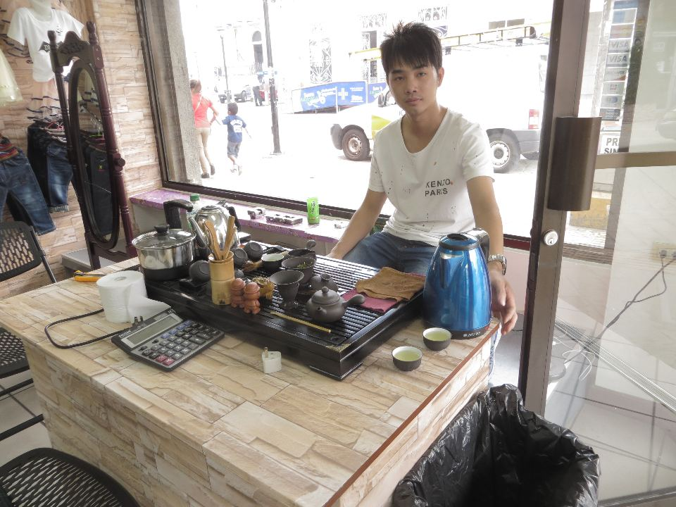 Young entrepreneur, Tony Wong, brews green tea in the picture window of his store. He offers tea to customers who come in to see his selection of children's clothing.