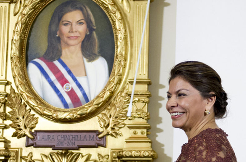 Former president Laura Chinchilla Miranda standing in front the portrait that now hands in the Hal of Presidents of the Legislative Assembly. The white dress is a contrast to the dark suits of all the other former presidents, all being male.