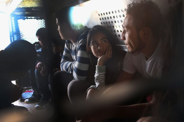 Central American immigrants wait to be transported after turning themselves in to Border Patrol agents near Rio Grande City. John Moore/Getty Images