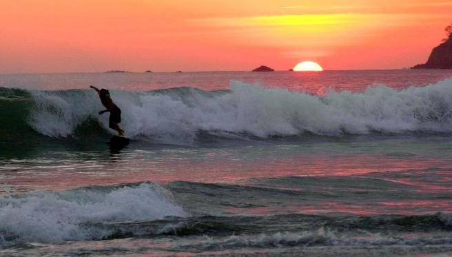 "A surfer catches a wave at sunset on a beach in Costa Rica. ""At sundown, everyone on the beach cheers the sunset, and a dozen teenage boys claim enough space to play soccer in the sand,"" writes Jim Meek. (KENT GILBERT / AP)"