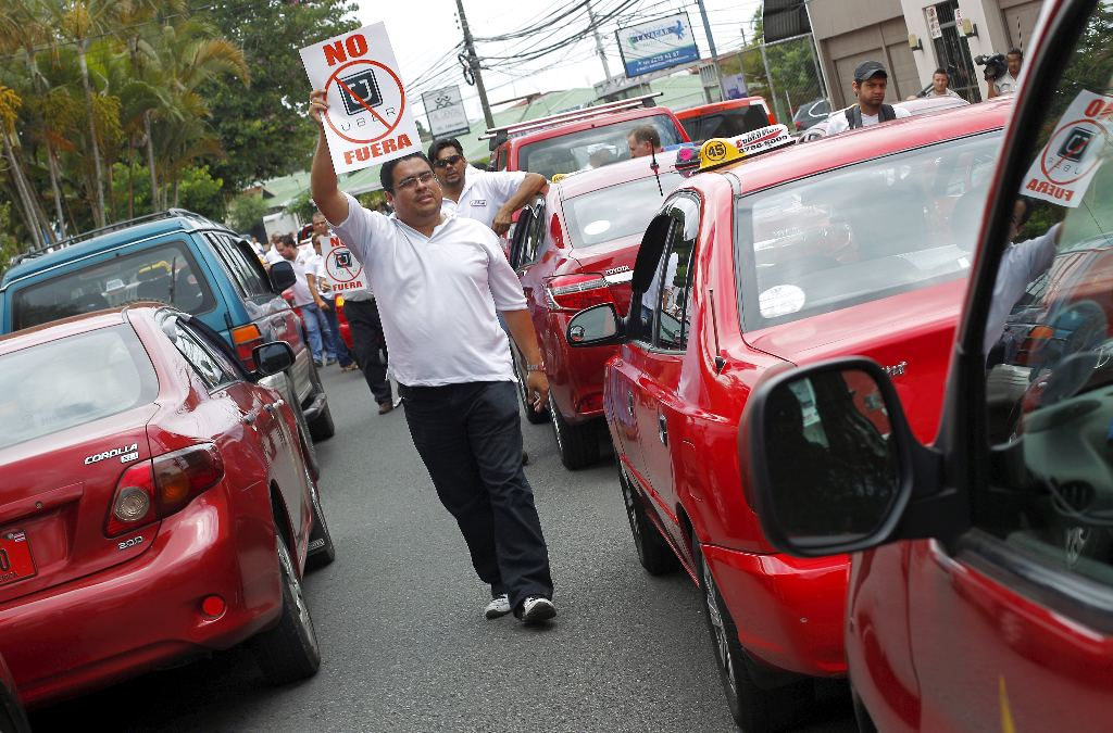 "A taxi driver holds a sign which reads ""No Uber, out"", during a protest against car-sharing service Uber."