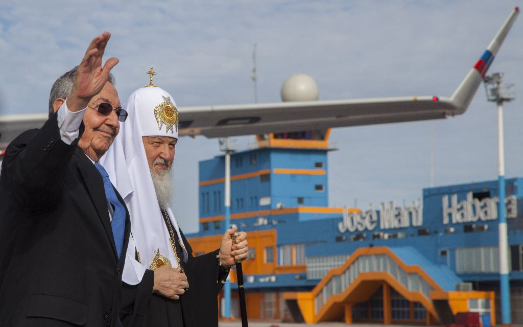 Russian Orthodox Patriarch Kirill, behind, walks with Cuba's President Raul Castro at the Jose Marti International airport in Havana, Cuba, Thursday, Feb. 11, 2016. Kirill is traveling through Latin America, visiting national leaders and the region's small Russian Orthodox communities. (Ismael Francisco/Cubadebate via AP)