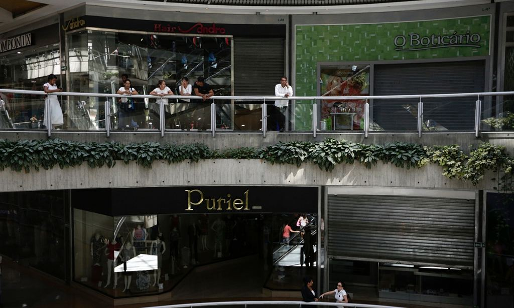 People wait outside closed stores at a mall in Caracas, Venezuela on Wednesday. Photograph: Marco Bello/Reuters