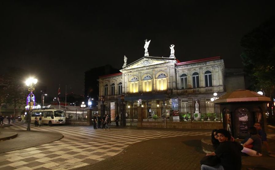 Image taken on Saturday March 19, 2016 shows people walking in front of the National Theatre (Teatro Nacional) with the majority of its lights off in the framework of the annual Earth Hour event in San Jose, Costa Rica.
