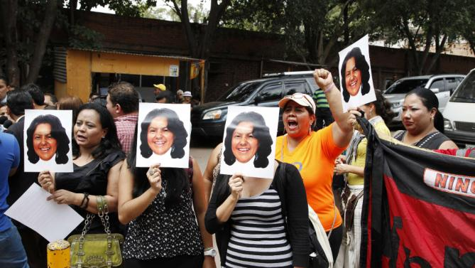People hold up photos of aslain Honduran indigenous leader and environmentalist Berta Caceres outside the coroners office in Tegucigalpa, Honduras, Thursday, March 3, 2016. Caceres, a Lenca indigenous activist who won the 2015 Goldman Environmental Prize for her role in fighting a dam project, had previously complained of receiving death threats from police, soldiers and local landowners because of her work. (AP Photo/Fernando Antonio)
