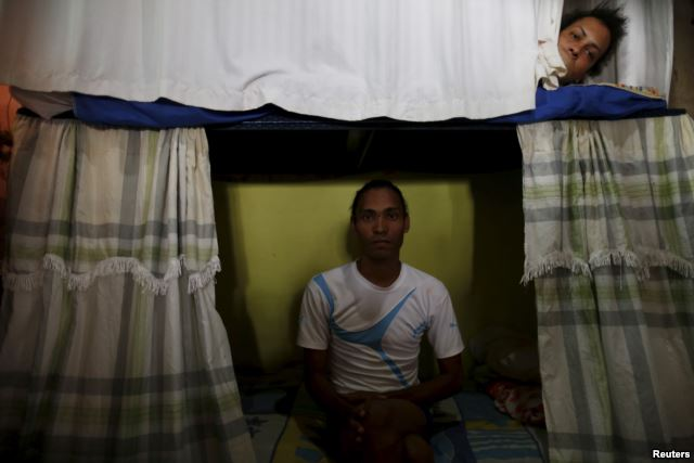 Inmate Alvis Javier (L), poses for a photograph as another prisoner looks from his bunk inside the transgender gallery in La Joya prison on the outskirts of Panama City, Panama