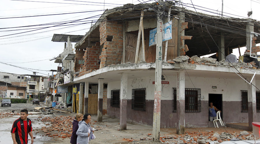 People walk by damaged buildings after an earthquake struck off Ecuador's Pacific coast. From Rt.com