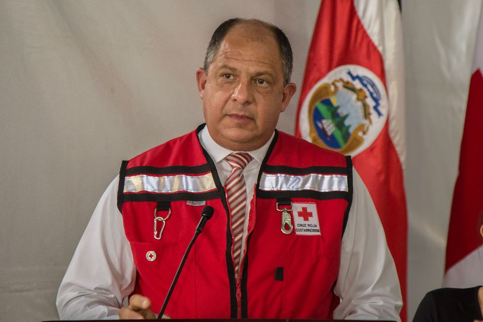 Wearing a Cruz Roja vest, President Luis Guillermo Solis signs the law that will . Photo Casa Presidencial