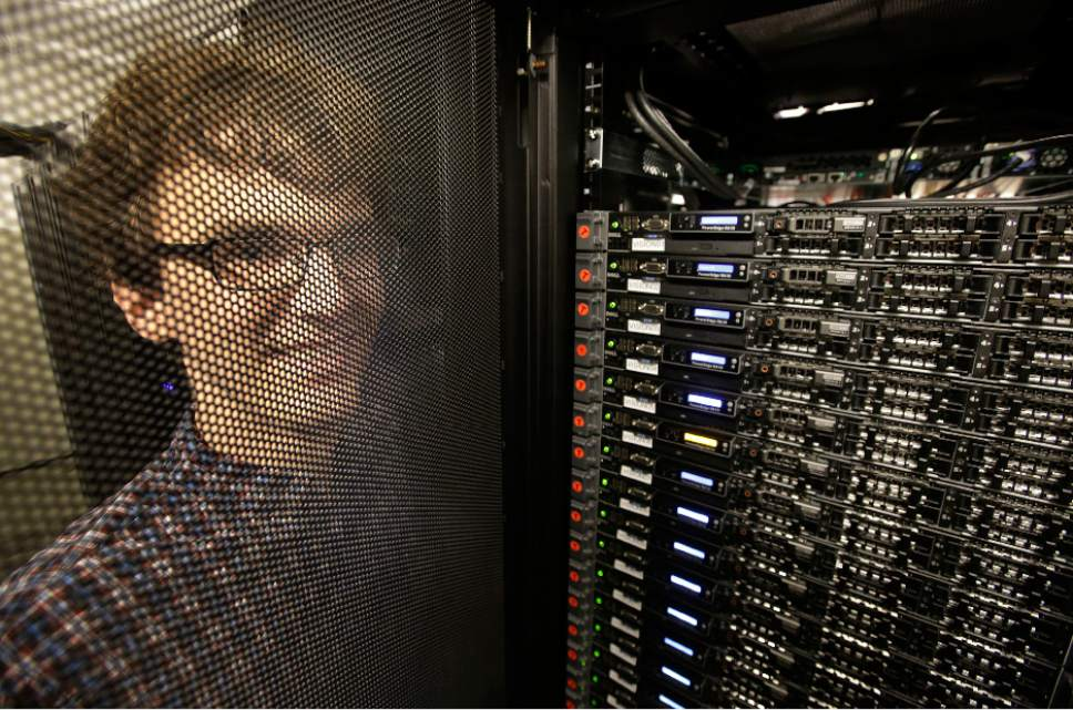 "In this Wednesday, June 22, 2016, photo, Massachusetts Institute of Technology researcher Carl Vondrick looks through a protective door while standing next to a computer server cluster, right, on the MIT campus, in Cambridge, Mass. MIT says a computer that binge-watched TV shows such as ""The Office,"" ""Big Bang Theory"" and ""Desperate Housewives"" learned how to predict whether the actors were about to hug, kiss, shake hands or slap high-fives, a breakthrough that eventually could help the next generation of artificial intelligence function less clumsily. (AP Photo/Steven Senne)"