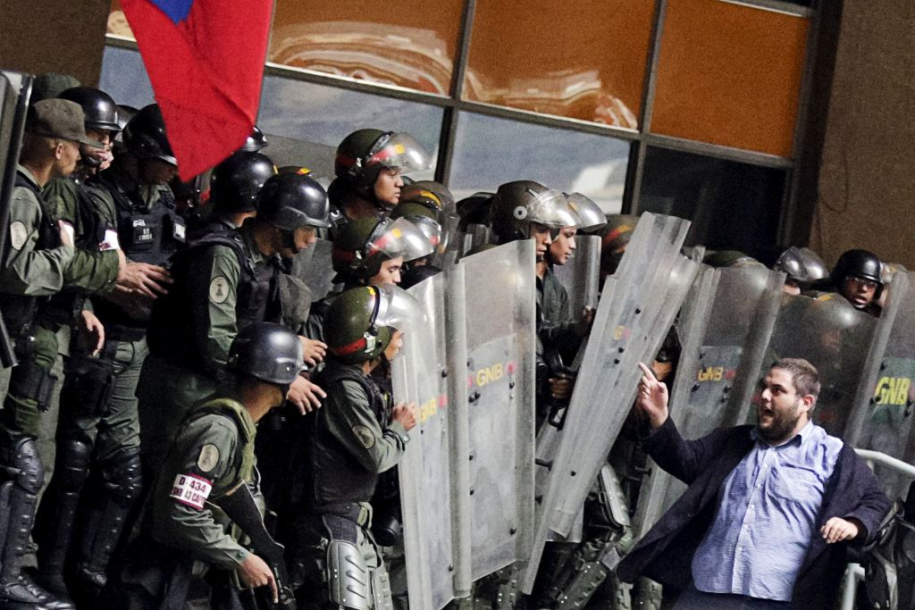 Juan Requesens, right, deputy of the Venezuelan coalition of opposition parties (MUD), argues with Venezuela's National Guards at the National Electoral Council (CNE) headquarters in Caracas, Venezuela, April 21, 2016.REUTERS/Marco Bello