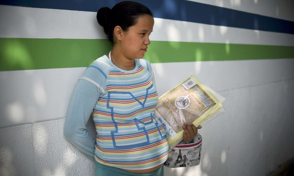A pregnant woman holds a mosquito net in Cali. With the end of the epidemic phase, Colombia has lifted the recommendation that women postpone pregnancy. Photograph: Luis Robayo/AFP/Getty Images