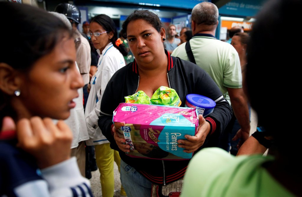 A woman holding food and other staple goods walks outside a supermarket in Caracas, Venezuela, June 30, 2016. REUTERS/Mariana Bazo