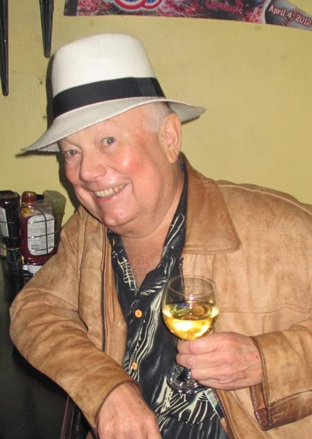 With his trademark white fedora, and a glass of Chilean white wine, Albert Brilliott (Alberto) flashes the smile that won him hundreds of friends in Downtown San José. Photo from Mark Wise.