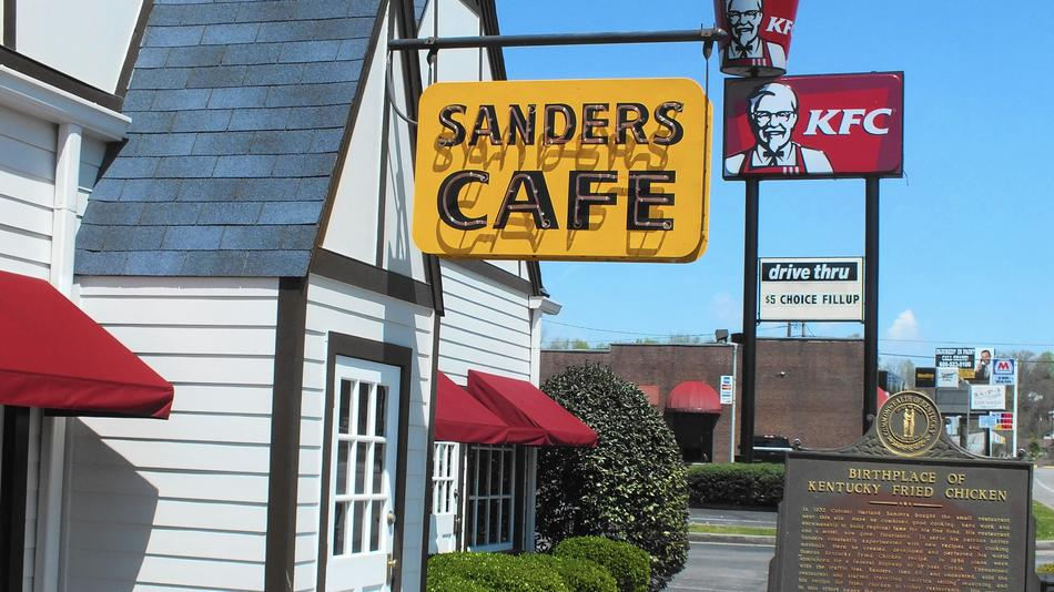 The original Sanders Cafe sign is small compared to the newer KFC sign and bucket that tower over the Corbin, Ky., restaurant.