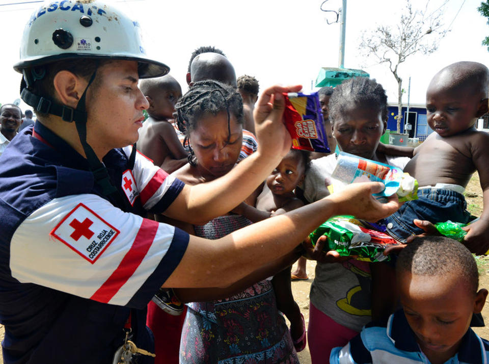 A Costa Rican Red Cross member distributes food to migrants in an encampment of Africans in Penas Blancas, Guanacaste, Costa Rica, on July 19. In a makeshift camp hundreds of tents shelter Haitians, Congolese, Senegalese and Ghanaian migrants waiting to continue their journey to the United States. Ezequiel Becerra/AFP/Getty Images