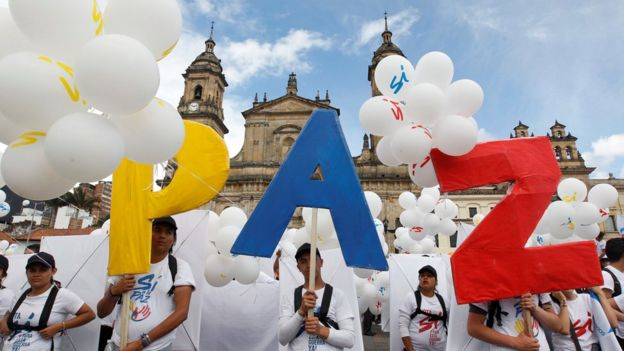 Correspondents say most Colombians are expected to support the deal - these supporters have made a sign of the Spanish word for