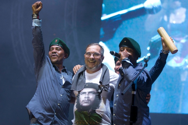 Rodrigo Londono, centre, also known as Timochenko, top leader of FARC, is embraced by singers of the Southern Rebels guerrilla band during a concert Sunday, Sept. 18, at the group's conference in the Yari Plains, Colombia. (Ricardo Mazalan/Associated Press)