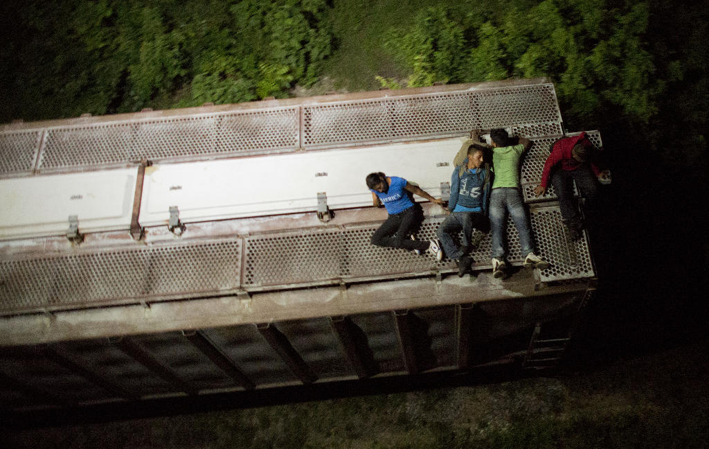 """a trial of impunity: thousands of migrants in transit face abuses amid mexico's crackdown. In this Aug. 26, 2014 photo, Central American migrants rest atop the last boxcar of a moving freight train as it heads north from Arriaga toward Chahuites, Mexico. A Mexican crackdown seems to be keeping women and children off the deadly train, known as """"The Beast,"""" that has traditionally helped thousands of migrants head north. The once-open route to the United States has become so difficult that trains now carry a small fraction of the migrants they used to, and almost exclusively adult men. (AP Photo/Rebecca Blackwell)"""