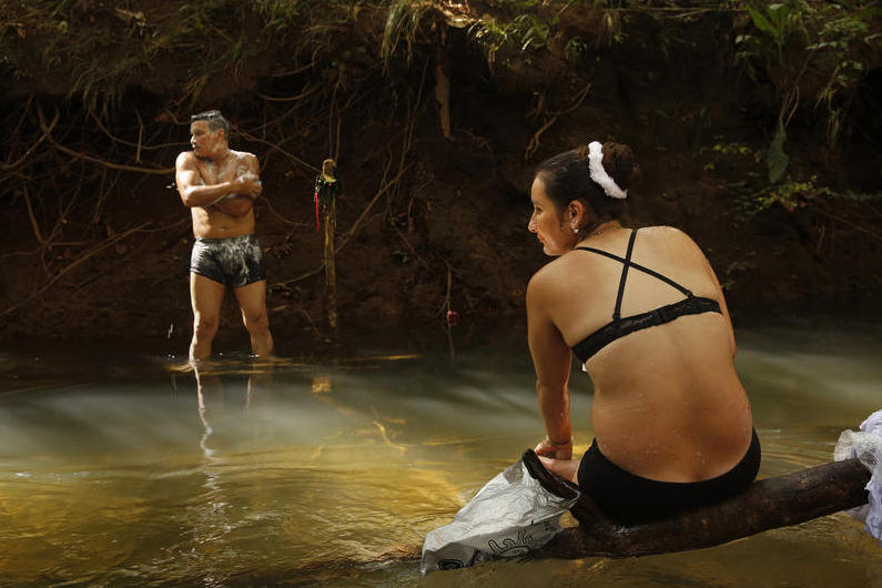 Revolutionary Armed Forces of Colombia member Viviana, 28, and her comrade Jon, 34, bathe in spring waters by their camp.