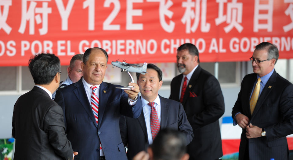 President Luis Guillermo Solis holding a model plane of the airplanes just outside donated by China
