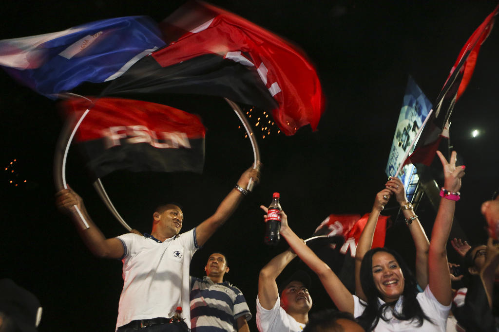 Supporters of Nicaragua's President Daniel Ortega and vice presidential candidate, his wife, Rosario Murillo wave flags of the Sandinista National Liberation Front, or FSLN, as Ortega won re-election, while celebrating in Managua, Nicaragua, Sunday, Nov. 6, 2016. Ortega won re-election to a third consecutive term as Nicaragua's leader, electoral officials said late Sunday as they released early results from an election that the opposition called a farce. (AP Photo/Esteban Felix)